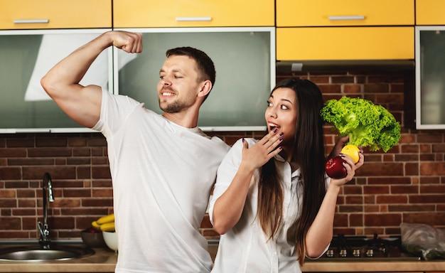 Gelukkige vrienden die voedsel voor diner voorbereiden, die in de groenten en de vruchten van de keukenholding stellen. man toont biceps op zijn arm. gezond eten bevorderen