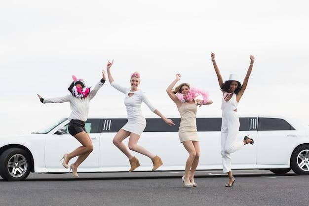 Gelukkige vrienden die voor een limousine springen