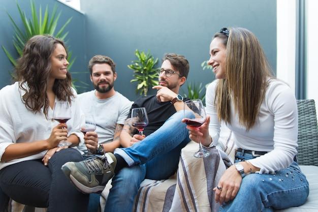Gelukkige vrienden die wijn drinken en babbelen