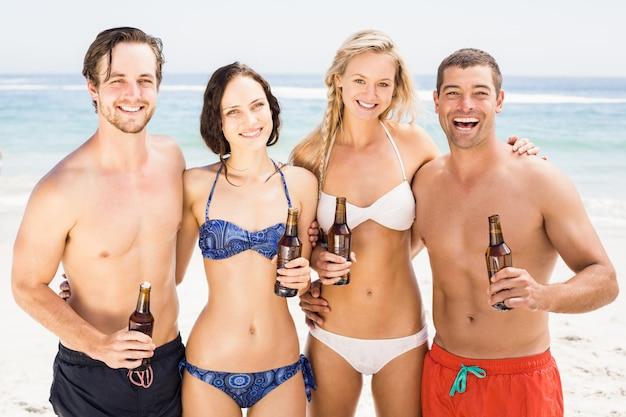 Gelukkige vrienden die zich op het strand met bierflessen bevinden