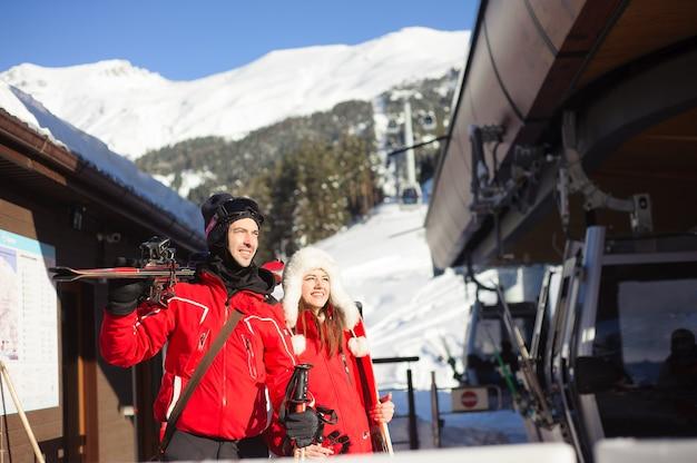 Gelukkige vrienden gaan skiën in de wintervakantie - jonge coulpe met plezier extreme sporten - vriendschap en vakantie concept