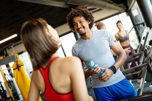 Gelukkige vrienden genieten van pauze tijdens het chatten in de sportschool