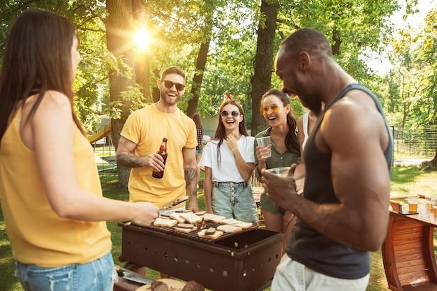 Gelukkige vrienden hebben bier en barbecue feest op zonnige dag