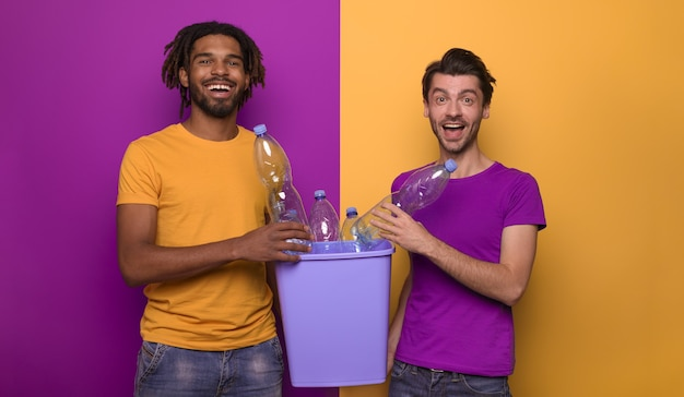 Gelukkige vrienden houden een plastic container vast met flessen in gele en paarse kleur.