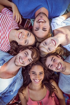 Gelukkige vrienden in een park die in cirkel samenkomen
