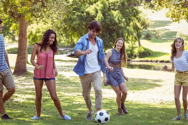 Gelukkige vrienden in het park met voetbal