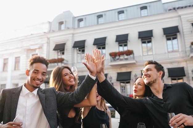 Gelukkige vrienden klappen in hun handen en lachen, genieten van zomeravond in de stad