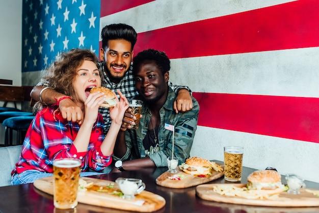 Gelukkige vrienden knuffelen, hamburgers eten, praten en glimlachen terwijl ze samen tijd doorbrengen in café.