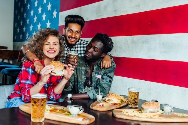 Gelukkige vrienden knuffelen, hamburgers eten, praten en glimlachen terwijl ze samen tijd doorbrengen in de gastropub.