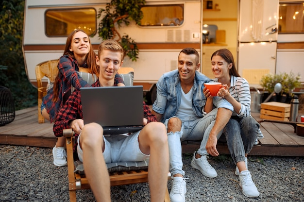 Gelukkige vrienden met behulp van laptop in de buurt van rv op picknick op kamperen in het bos