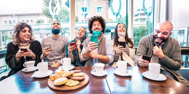 Gelukkige vrienden met behulp van mobiele slimme telefoons bij koffiebar