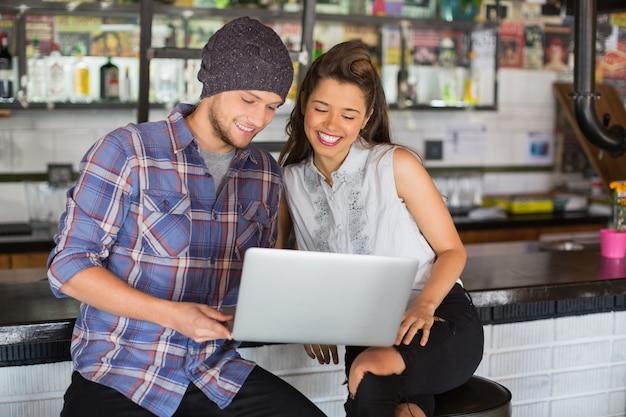 Gelukkige vrienden met laptop in restaurant