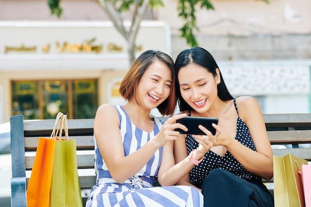 Gelukkige vrienden met telefoon buitenshuis