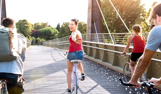 Gelukkige vrienden millennial plezier fietsen in stadspark