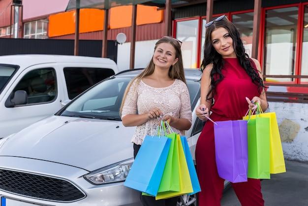 Gelukkige vrienden na het winkelen op de parkeerplaats in de buurt van winkelcentrum
