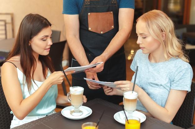 Gelukkige vrienden praten op zoek elkaar zitten in de tabel van een bar met de ober