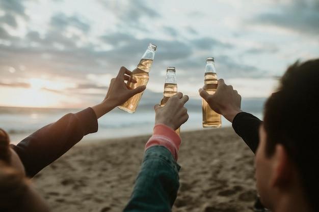 Gelukkige vrienden roosteren op het strand