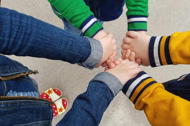 Gelukkige vrienden stapelen hand bij elkaar.