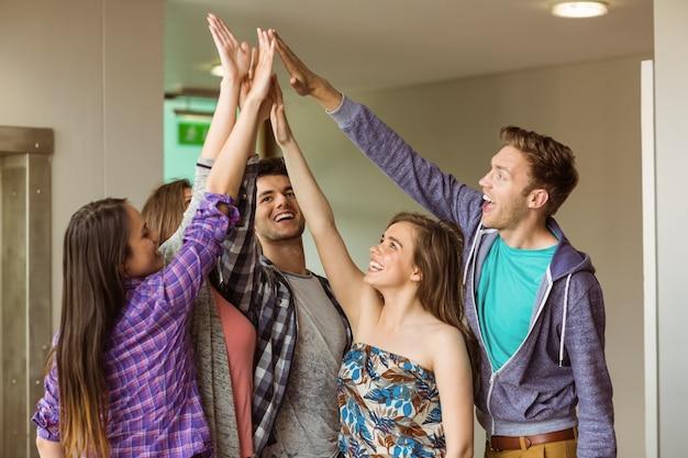 Gelukkige vrienden studenten high five voor hun teamwork