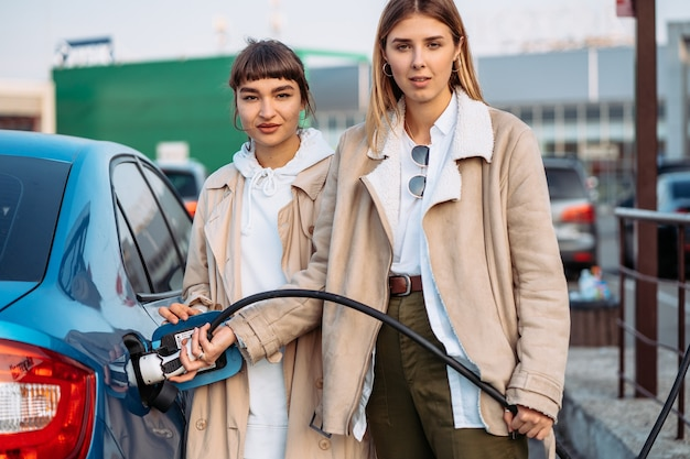 Gelukkige vrienden tanken auto in benzinestation. vakantiereis van vrienden
