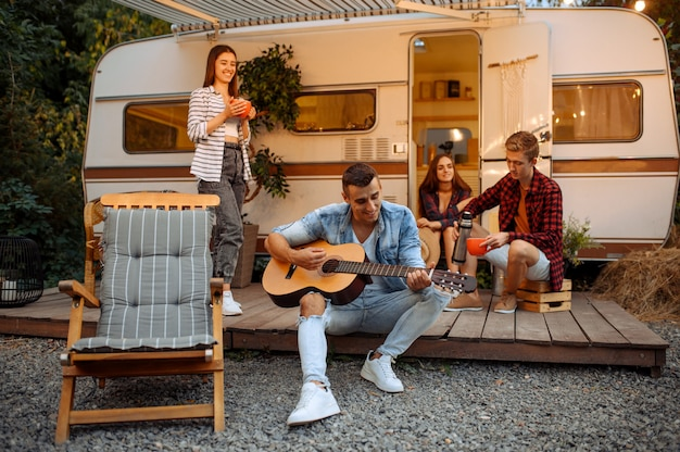 Gelukkige vrienden zingen liedjes met gitaar op picknick op camping in het bos. jongeren die zomeravontuur beleven op camper, kampeerauto twee vrijetijdsparen, reizend met aanhanger