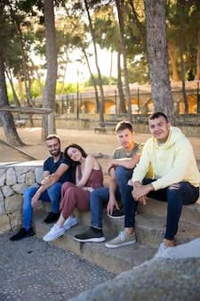 Gelukkige vrienden zitten op de trappen van een park met pijnbomen
