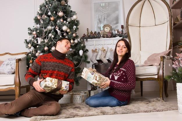 Gelukkige vrienden zitten op de vloer met geschenkdozen in de buurt van de prachtige kerstboom en de grote elegante stoel.