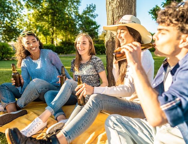 Gelukkige vriendengroep buiten in stadspark bier drinken uit fles vieren zittend op gras. zorgeloze jonge lachende mensen die plezier hebben in de natuur met alcohol bij zonsondergang genieten van een picknick in het gras