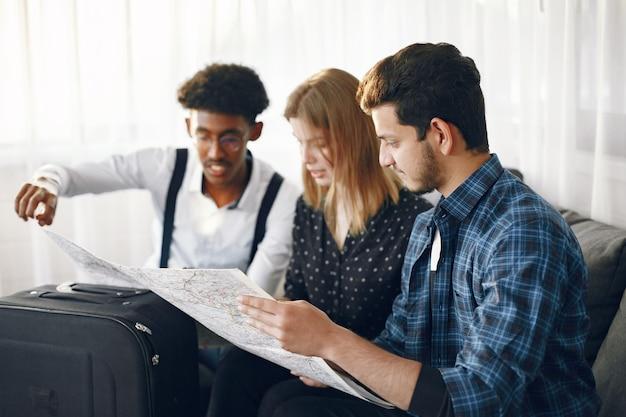 Gelukkige vriendenkring die een reis plant. globetrotters inspecteren een kaart die thuis is. europese en indiase etniciteit.