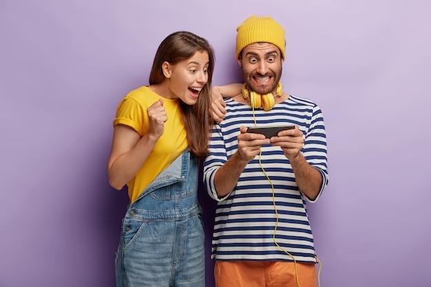 Gelukkige vriendin en vriend genieten van nieuw spel, tevreden zijn met nieuwe smartphonefuncties, staren naar het scherm van gadget, gekleed in modieuze kleding, juichen om online marathon te winnen, verslaafd zijn