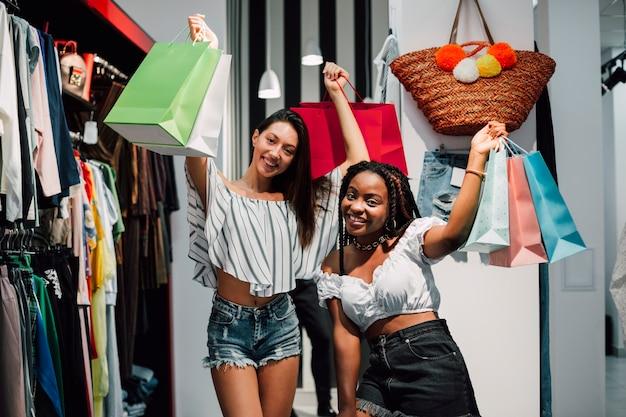 Gelukkige vriendinnen houden boodschappentassen