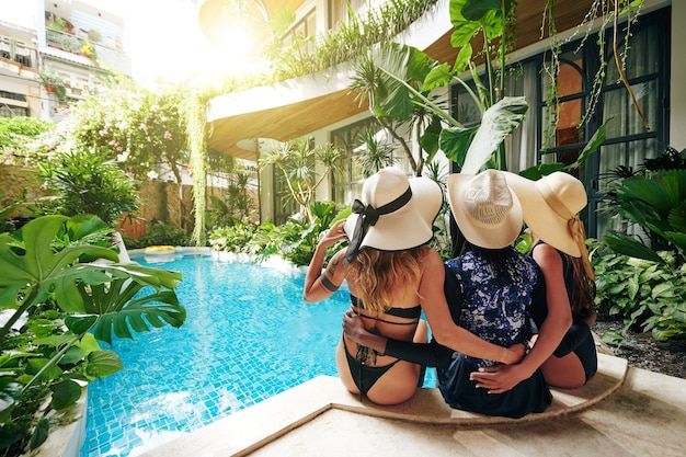 Gelukkige vriendinnen in strohoeden en zwemkleding die op de rand van het spa-hotelzwembad zitten, knuffelen en genieten van een zonnige zomerdag