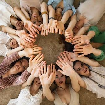 Gelukkige vriendinnen liggen cirkel die handen opheft die samen genieten van vriendschapssamenwerking