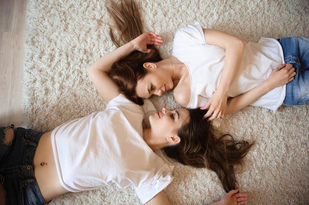 Gelukkige vriendinnen liggend op terug bovenaanzicht zussen.