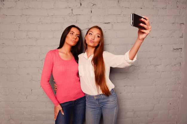 Gelukkige vriendinnen maken selfie-foto's op een mobiele telefoon