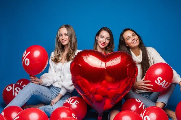 Gelukkige vriendinnen zitten met veel luchtballonnen om hen heen, foto geïsoleerd op blauwe muur