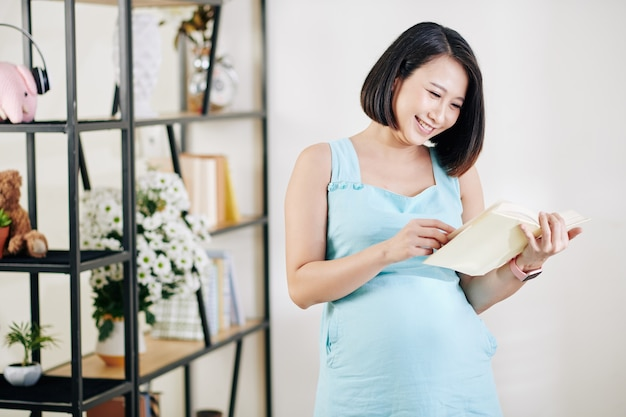 Gelukkige vrij jonge vietnamese zwangere vrouw die interessant boek over zwangerschap en ouderschap leest