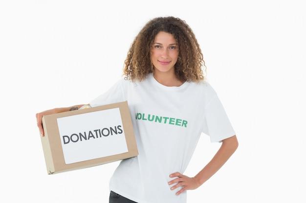 Gelukkige vrijwilliger die een doos van schenkingen met hand op heup houdt