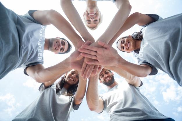 Gelukkige vrijwilligers die hun handen samenbrengen