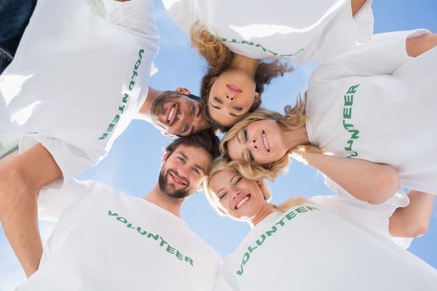 Gelukkige vrijwilligers vormen een kruiper tegen blauwe hemel