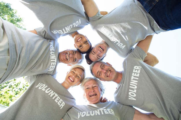 Gelukkige vrijwilligersfamilie die neer de camera bekijken
