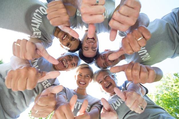 Gelukkige vrijwilligersfamilie die neer met omhoog duimen kijkt