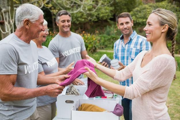 Gelukkige vrijwilligersfamilie die schenkingenmaterialen scheidt
