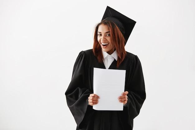 Gelukkige vrolijke afrikaanse vrouw gediplomeerde het glimlachen holdingstest.