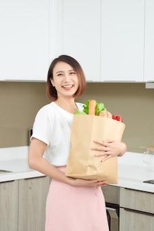 Gelukkige, vrolijke aziatische vrouw met papieren zak vol verse producten, groenten, groenten, stokbrood en bananen.