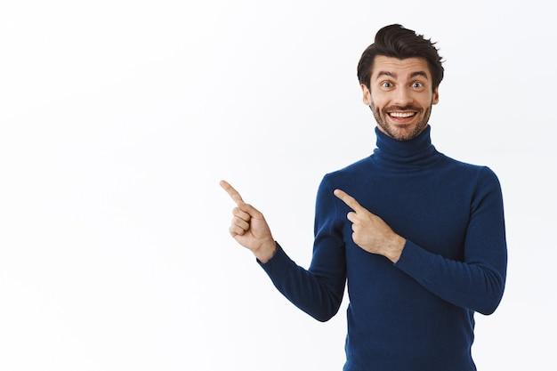 Gelukkige vrolijke bebaarde man in blauwe trui, geweldig product aanbevelen, glimlachend onder de indruk, wijzend naar de linkerbovenhoek, iets promoten over een witte muur
