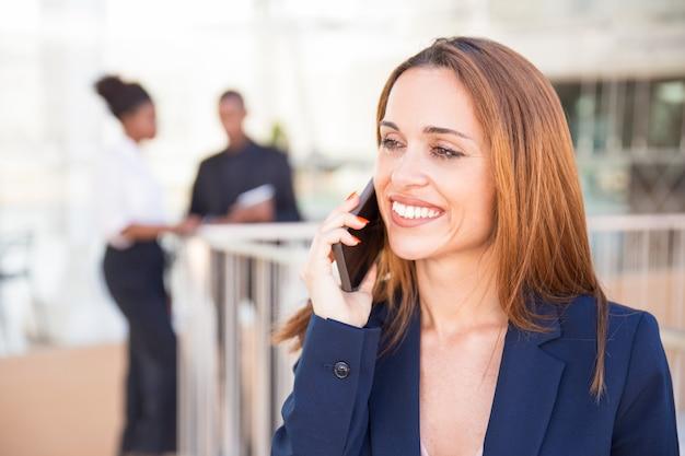 Gelukkige vrolijke bedrijfsdame die op cellphone spreekt