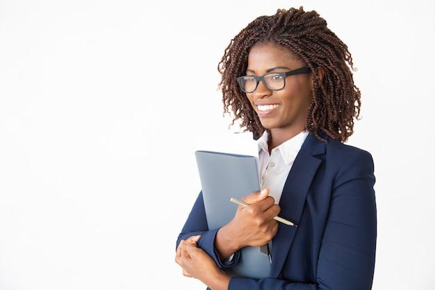 Gelukkige vrolijke bureaumedewerker die in glazen documenten houdt