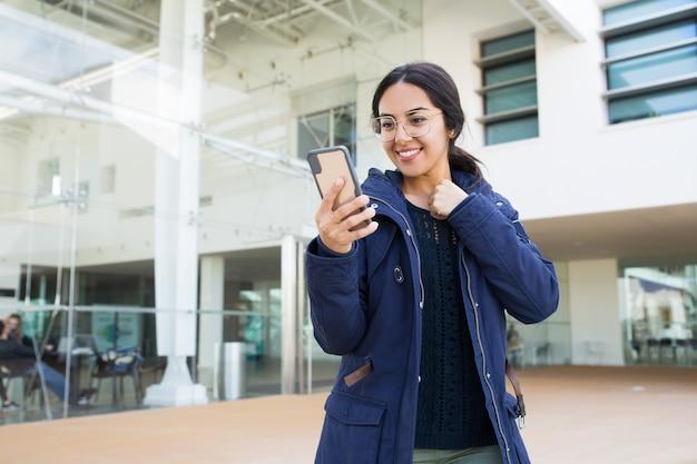 Gelukkige vrolijke bureauwerknemer die online app gebruiken