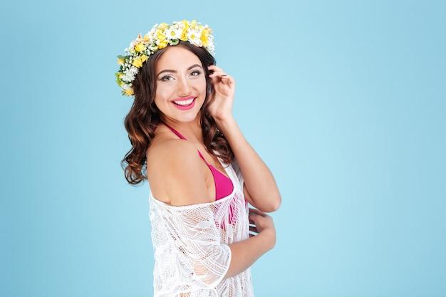 Gelukkige vrolijke dame die bloemdiadeem draagt dat op de blauwe achtergrond wordt geïsoleerd